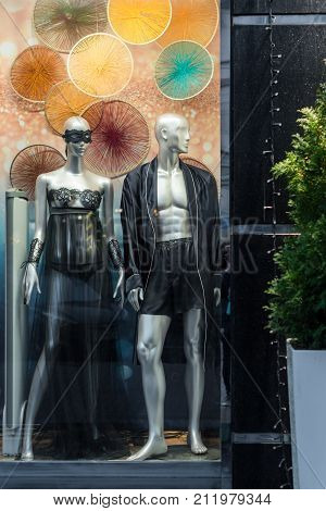 Male and female mannequins in sexy or carnival underwear at night showcase. Clothing and lingerie