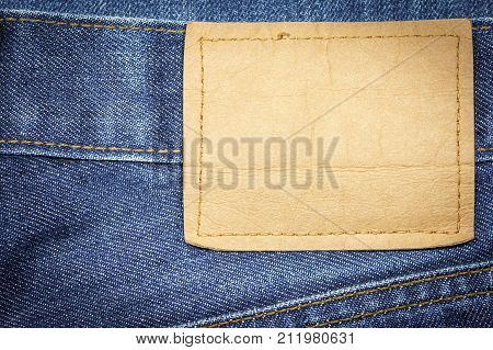 Denim jeans fabric texture or denim jeans background with blank leather label for beauty clothing. fashion business design and industrial construction idea concept.
