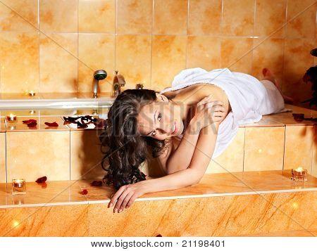 Woman sitting on edge of sauna.