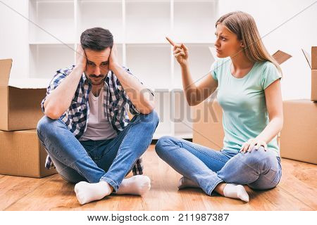 Young couple is moving in their new home. They are arguing.