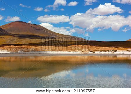 Color of Atacama Desert under blue sky with high clouds in Chile South America. Wonders of Atacama landscape with lagoon salt deposits and volcanic mountains.