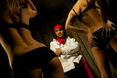Pirate  with pair Sexy passionate girls against wooden background poster