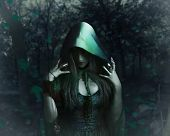 Beautiful sorceress in green cloak holding antique watch standing in the night forest photo. poster
