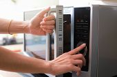 Woman's Hands Closing Microwave Oven Door And Preparing Food in microwave. poster