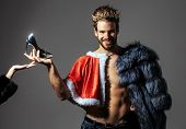 Freak gay and transvestite. Christmas guy in santa fur coat in crown. Cinderella prince with shoe on grey background. Drag queen homosexual and trans. poster