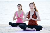 Young healthy asian women practicing yoga in namaste posture on the beach healthy lifestyles wellness well being poster