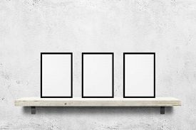 Еркуу цhite blank photo frames mockup on shelf over white concrete wall background