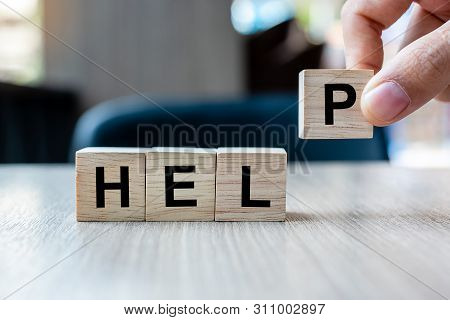 Businessman Hand Holding Wooden Cube Block With Help Business Word On Table Background. Help, Hope,