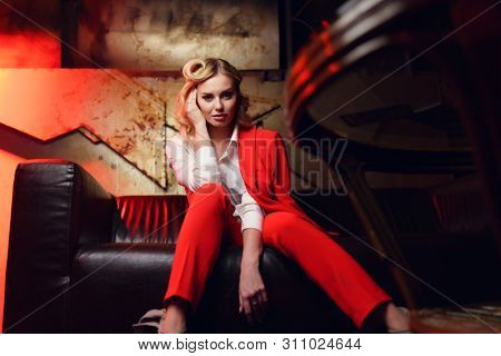 Full-lenght photo of young blonde in red jacket sitting on leather sofa