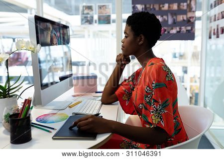 Side view of beautiful young African American female graphic designer using graphic tablet at desk in office. This is a casual creative start-up business office for a diverse team