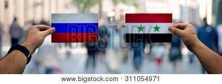 Two Hands Holding Different Flags, Russia Vs Syria On Politics Arena Over Crowded Street Background.