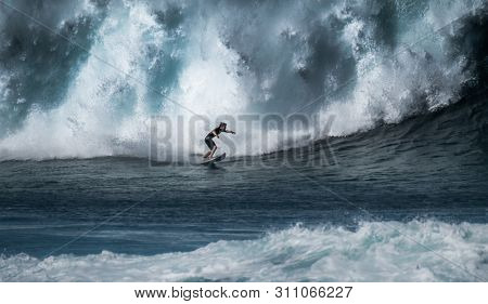 OAHU / USA - DECEMBER 05, 2019: Surfer rides giant wave breaking at the famous Banzai Pipeline surf spot located on the North Shore of Oahu in Hawaii