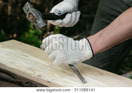 Carpenter is working by a chisel and hammer with a wooden board on his workbench. poster
