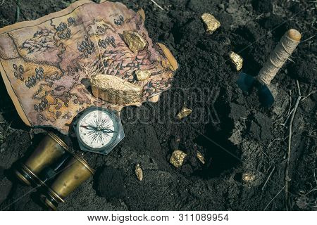 Treasure Map, Compass, Binoculars And Golden Nuggets On A Ground. Treasure Hunt Concept Background.