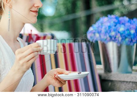 Young Beautiful Girl In A White Dress Close Up Is Drinking Coffee In A Cafe Outdoors