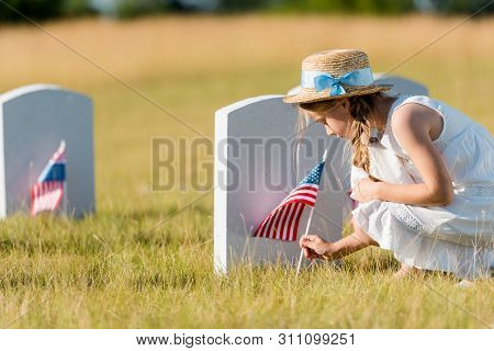 selective focus of adorable kid in straw hat sitting near headstone with american flag in graveyard poster
