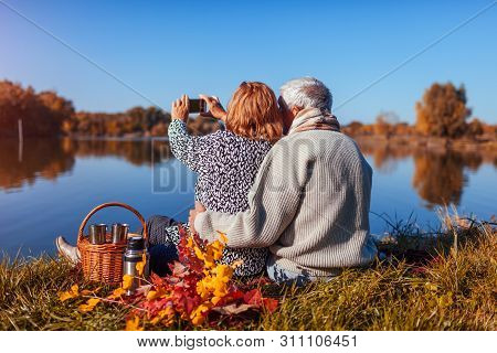 Senior Couple Taking Selfie While Having Picnic By Autumn Lake. Happy Man And Woman Enjoying Nature
