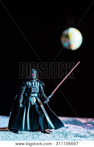 Kyiv, Ukraine - May 25, 2019: Darth Vader Figurine With Lightsaber On Black Background With Planet E