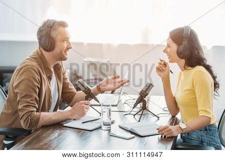 Two Radio Hosts In Headphones Talking While Recording Podcast In Radio Studio