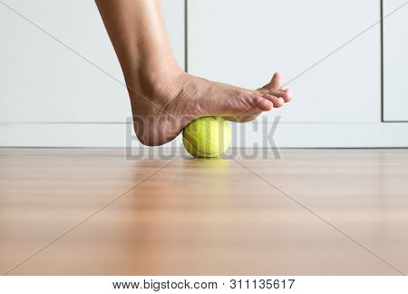 Woman Massage With Tennis Ball To Her Foot In Bedroom,feet Soles Massage For Plantar Fasciitis,close