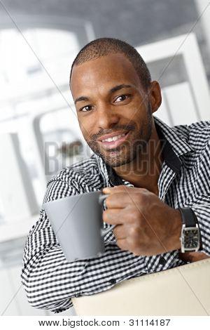 Portrait of happy goodlooking afro office worker guy on coffee break.