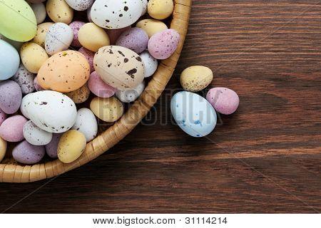 Foto de Still life de doces salpicados coberto chocolate ovos de Páscoa dentro de um cesto de vime em uma madeira rústica