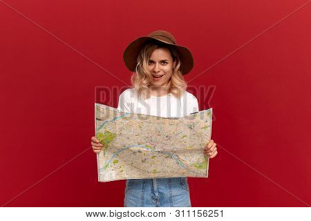 Happy Blond Girl With Curly Hair In A White T-shirt And A Sundown Hat Holds Map Looking For Itinerar