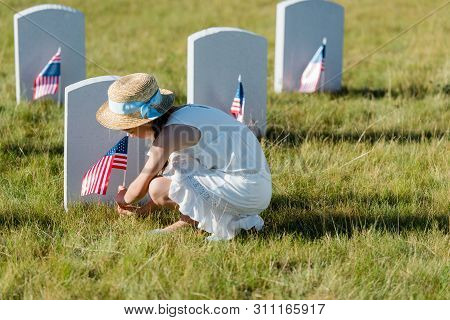 selective focus of kid in straw hat sitting near headstone with american flag in graveyard poster