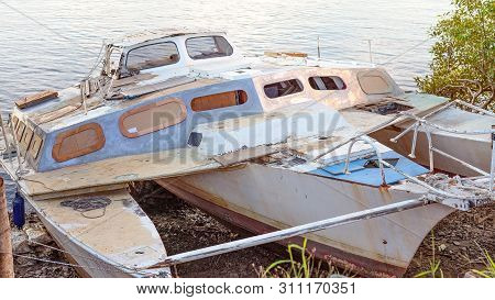 A Decrepit Damaged Old Wooden Catamaran Abandoned In A State Of Disrepair Run Ashore On A Mangrove R