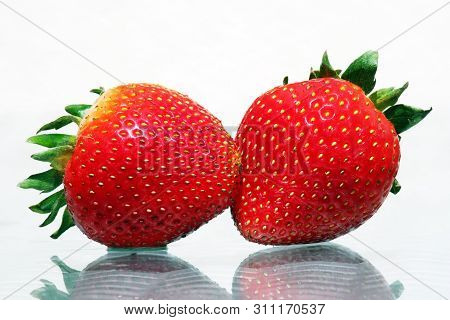 Close Up Of Two Strawberries With Reflections Against High Key Background. Choose A Focal Point.