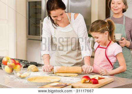 Mother and daughter making apple pie together grandmother check recipe