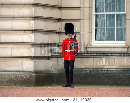 London, Uk - April, 2019: Queens Guard - Buckingham Palace. English Guard Patrolling In London. Soli