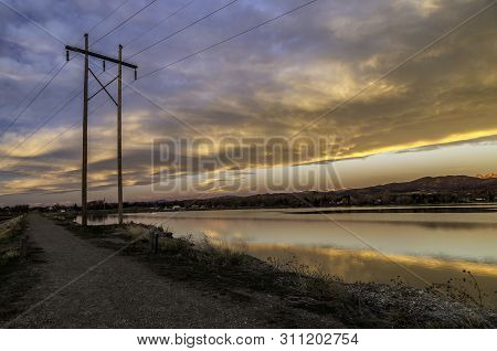 Electricity Poles At Sunrise With Colorado Mountains And Lake Background