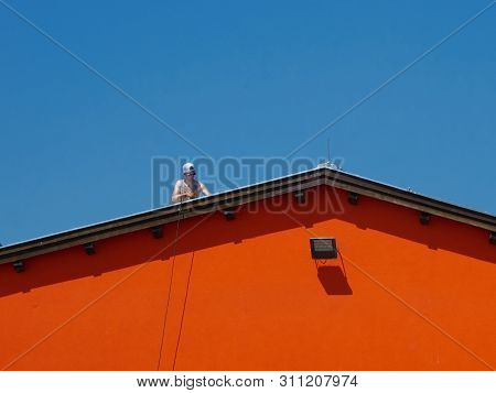 Vienna - 5 June 2019: Shirtless Man Working On A Roof Of An Industrial Compound Without Security Ele