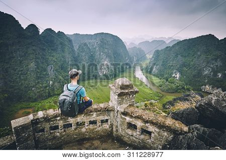 Traveler In Vietnam. Pensive Young Man With Backpack Sitting On Peak Mua Cave. Ninh Binh Province, V