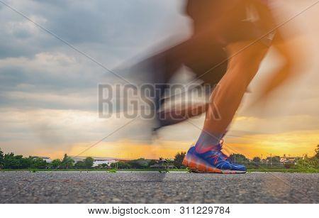 Runner's Feet, Motion Blurred Runner Closeup Shot Runner Running At A Fast Pace Background Sky Sunli