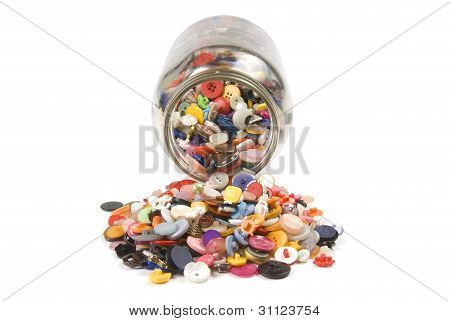 Buttons spilling out of a jar on a white background