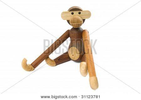 Toy wooden monkey sitting on a white background.