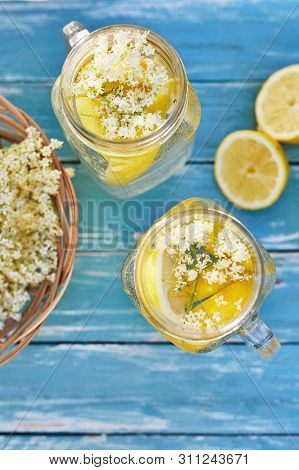 Top View Of Elderflower Lemonade With Basket Of Elderberry Flowers On Wooden Table
