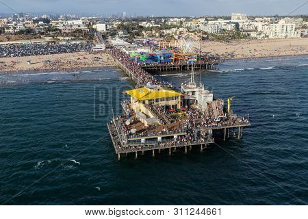 Santa Monica, California, USA - August 6, 2016:  Aerial view of busy summer crowds on popular Santa Monica Pier near Los Angeles.