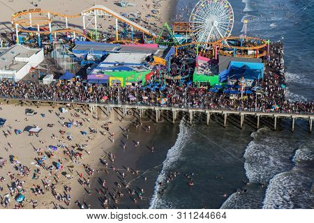 Santa Monica, California, USA - August 6, 2016:  Aerial view of busy summer crowds at popular Santa Monica Beach and Pier near Los Angeles.