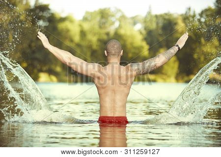 Muscle Tattooed Man Execising In Summer City Lake Water