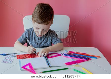 Portrait Of Cute Kid Boy At Home Making Homework. Little Concentrated Child Writing With Colorful Pe