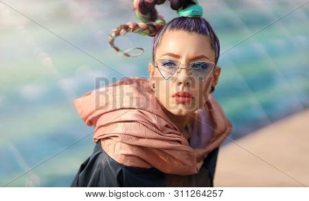 The avant-garde portrait girl with unusual make up and fancy sun glass. Portrait of young woman chilling in the sun. Woman with avant-garde hair and bright make-up. Fashionable urban toning poster