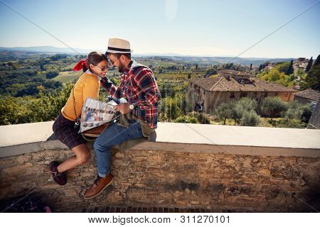 Smiling romantic man and girl using map as guide on vacation.