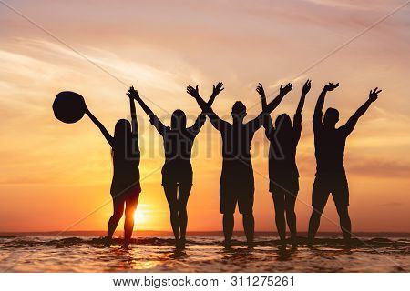 Five Happy Friends With Raised Hands Having Fun At Sunset Beach. Photo Of Silhouettes