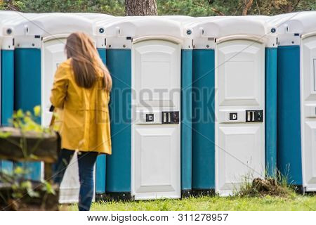 Girl Going Into Portable Toilet In A Park.