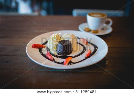 The Picture Of Hot Chocolate Lava Cake With Vanilla Ice Cream And Fresh Strawberry