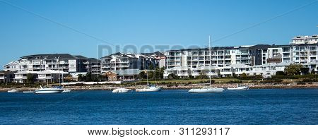 Large Waterside Houses, Apartment Condominiums In Suburban Community On Riverfront With Boats On Wat