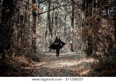 Halloween Daemon With A Knife Runs Through The Woods